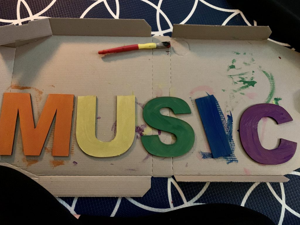 Painting the wooden letters, that spell out 'Music' in rainbow colours