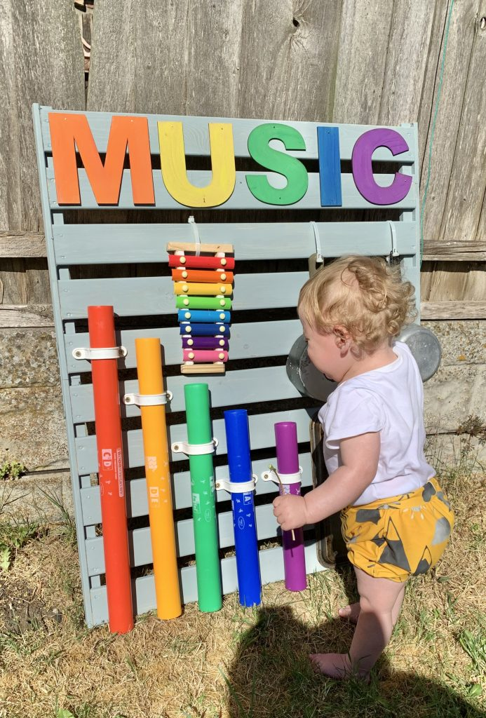 Blonde toddler stood up playing with the finished music wall