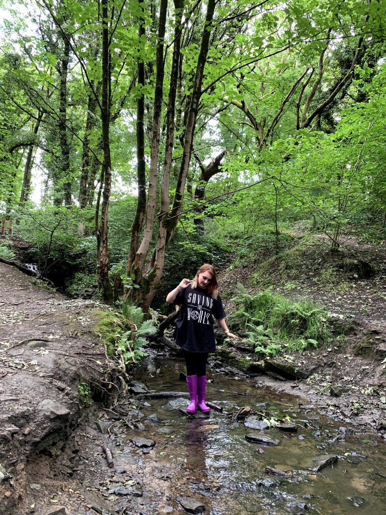 "A girl wearing purple wellies and a black top that says ""Saving the world"" stood in a stream in the middle of a forrest"
