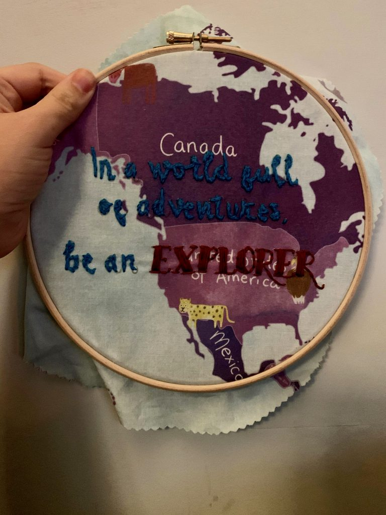 """Embroidery in a hoop. that says """"in a world full of adventure, be an explorer"""""""