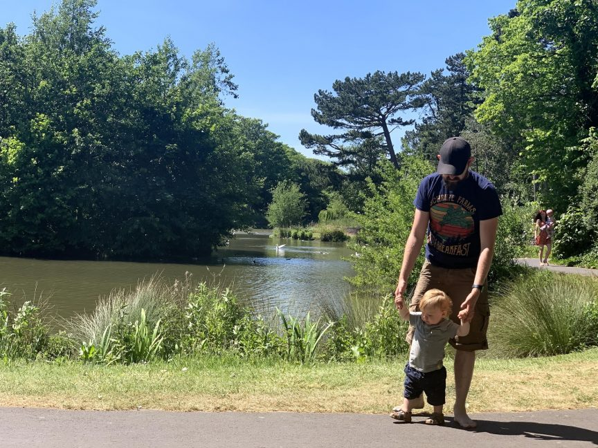 A man and his son, holding hands walking by a lake