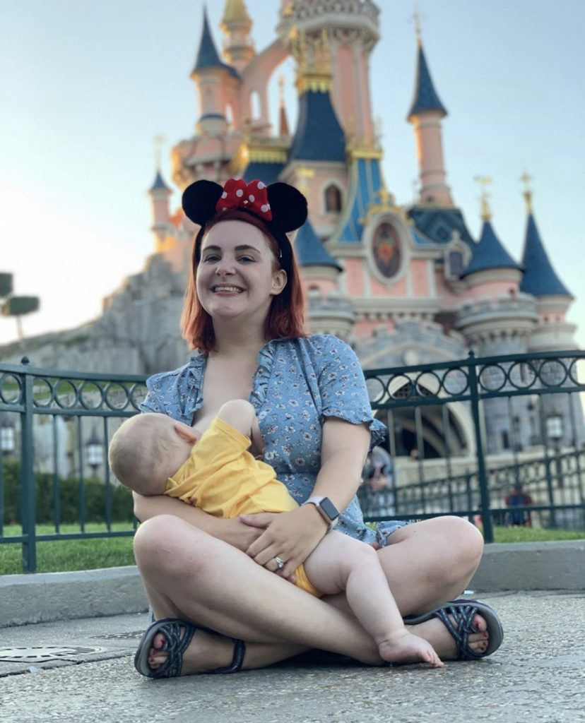 A mum breastfeeding a baby. The mum is wearing Minnie Mouse ears and sitting in front of the Disney castle in Paris