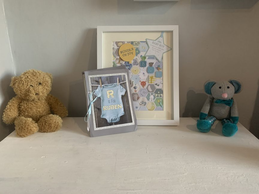Keepsake card frame and book sat on a white surface next to two teddies