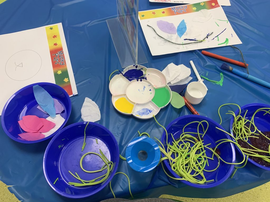 A table of blue bowls, some green spaghetti, paint and bits of tissue paper