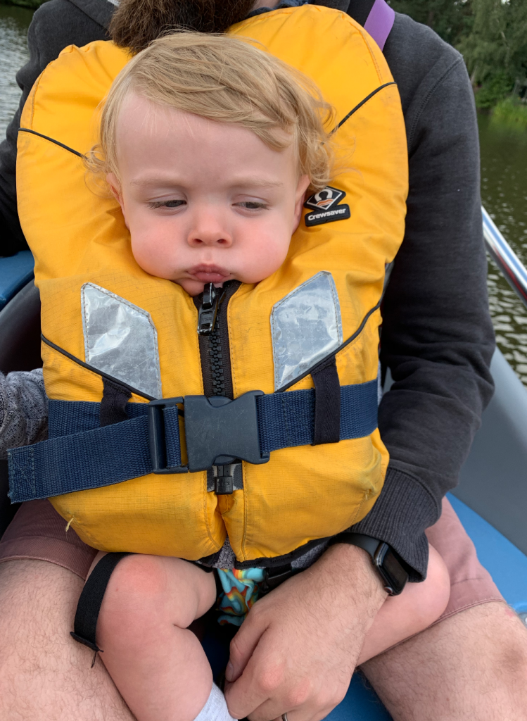 A toddler, wearing a yellow life-jacket. It's quite tight and has made his face look squashed