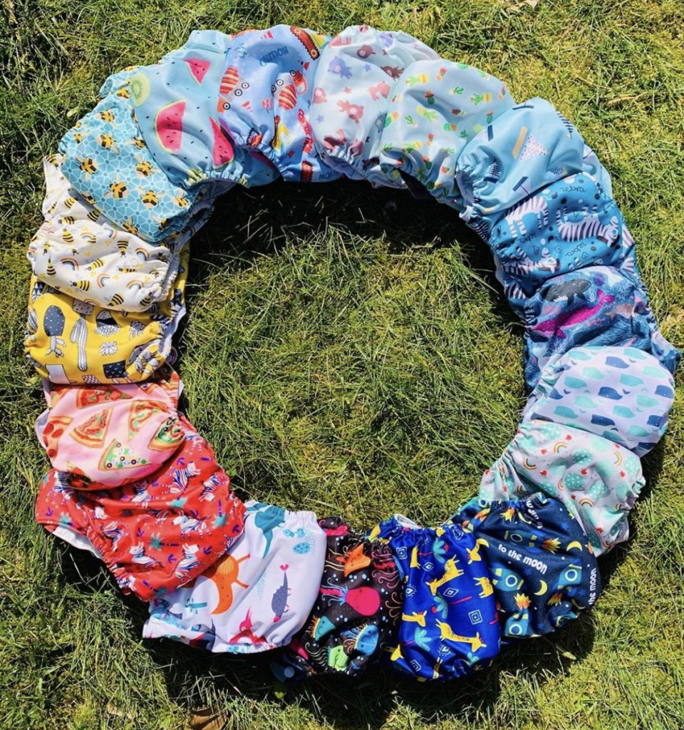 A circle of cloth nappies featuring prints like bees, pizza, dinosaurs, rockets and animals