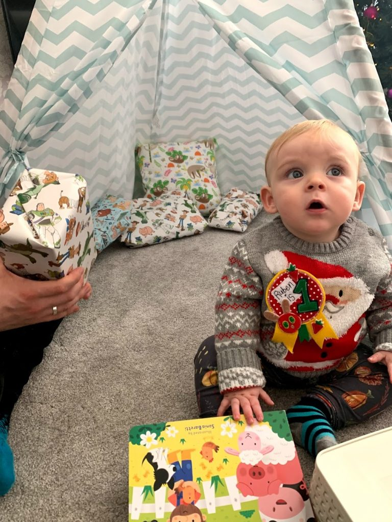 A baby with a christmas jumper on, with presents around him and a tent behind